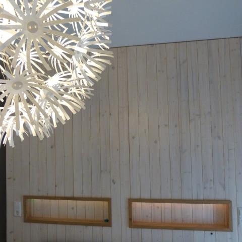 Trennwand aus Rauspundschalung weiß Lasiert mit integrierten Nachttischen und LED Beleuchtung. Dahinter ein begehbarer Kleiderschrank mit Fachböden die durch Schiffstaue gehalten werden